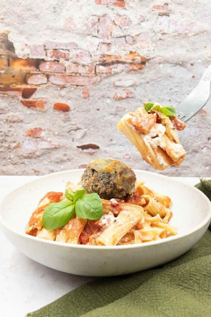 A bowl of vegetarian baked pasta, with a fork full of rigatoni pasta, tomatoes and fresh bail.