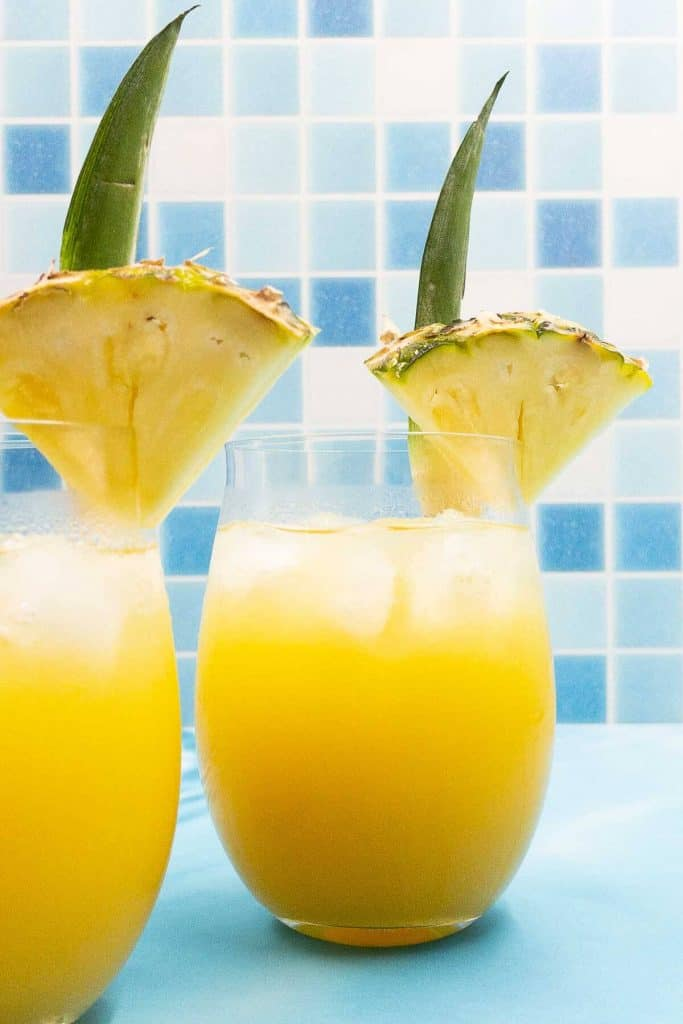 Two delicious pineapple tequila cocktails, freshly made with pineapple wedge garnish.