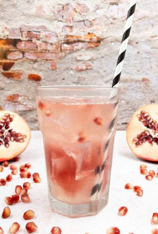 A homemade tequila el diablo rojo in a highball glass with a straw and pomegranate seeds.