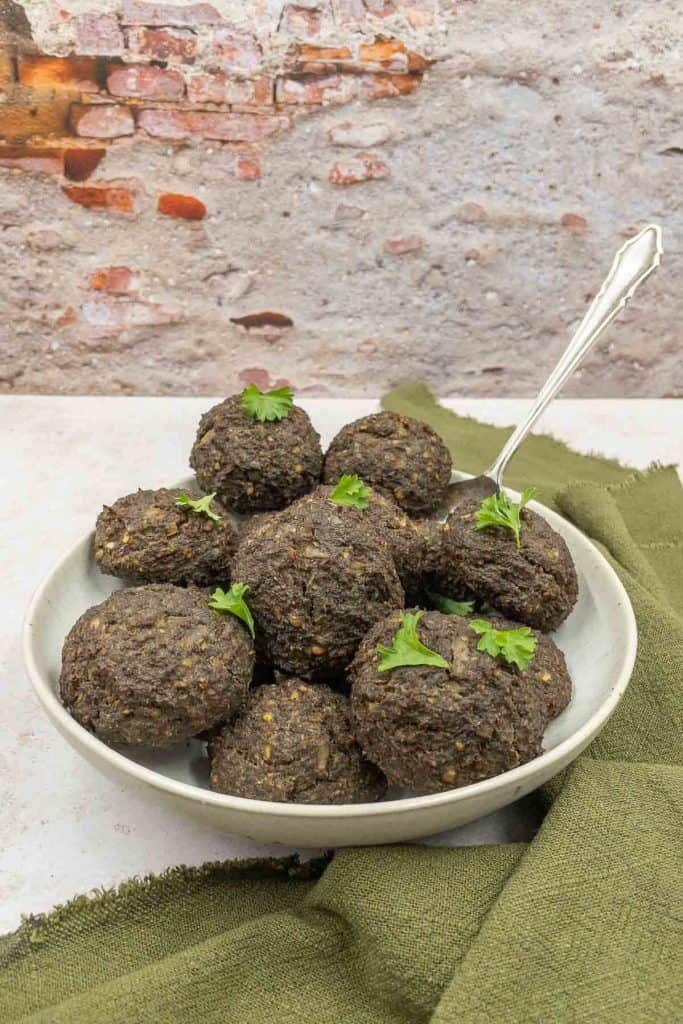 Freshly made vegetarian meatballs with parsley, a spoon and a green linen napkin.