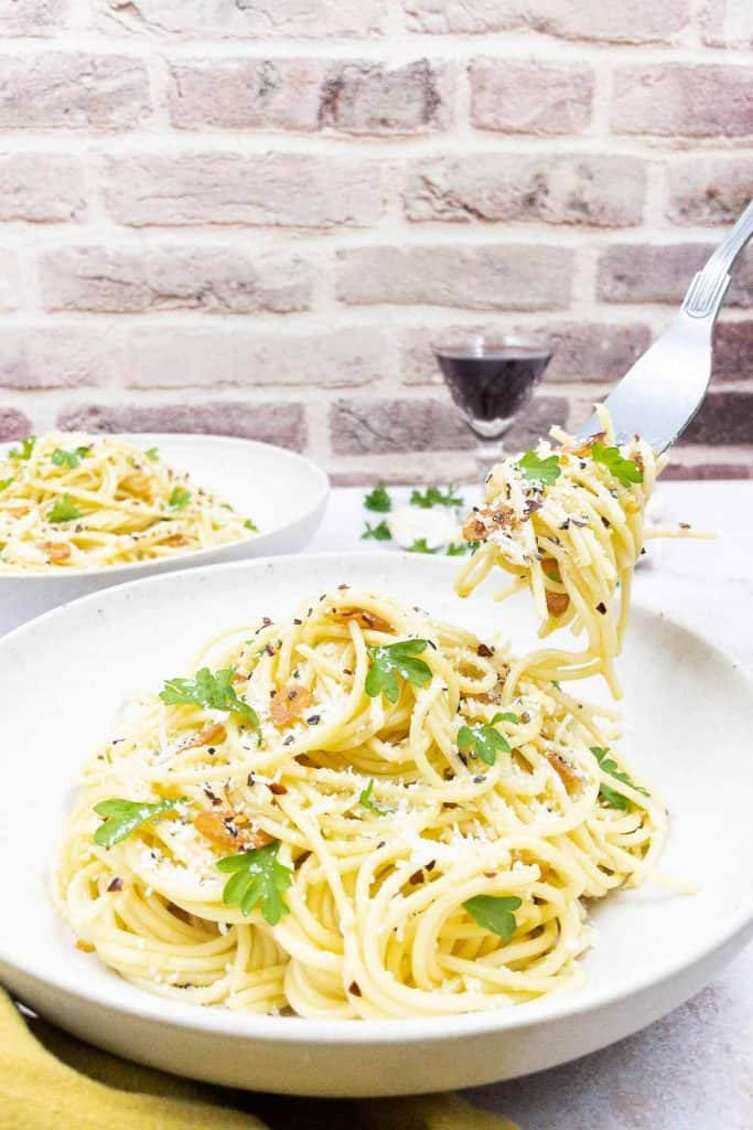 A bowl of homemade spaghetti aglio e olio, with freshly grated parmesan cheese and parsley.