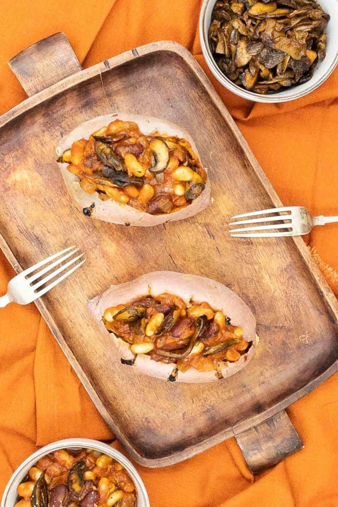 Oven baked sweet potatoes with crispy skin and a BBQ beans topping.