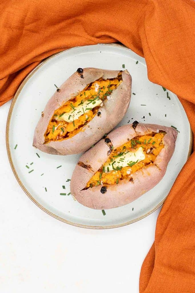 Fresh baked sweet potato, with a garnish of chives, salt and butter.