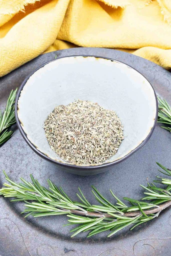 A bowl of homemade Italian seasoning with sprigs of rosemary.