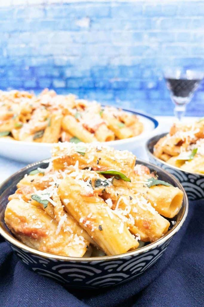 Bowls of pasta with pink sauce, a tomato cream sauce, garnished with fresh basil.