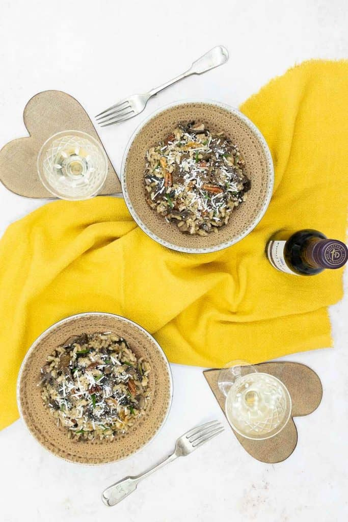 Bowls of freshly made mushroom risotto, white wine and grated parmesan cheese.